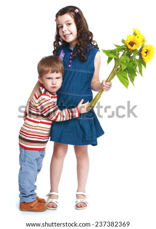 Little brother embracing his sister who is holding a bouquet of flowers.Isolated on white background portrait. - stock photo