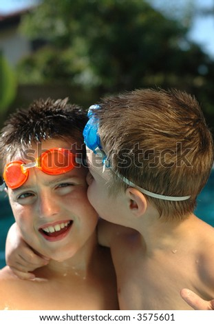 Little brother kissing his older brother in the pool - stock photo