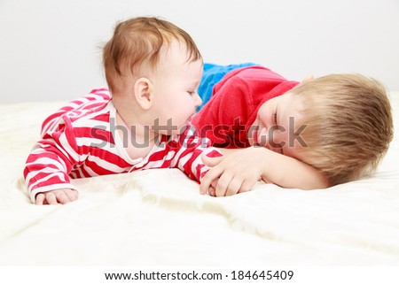 little brother playing with newborn sister, family concept - stock photo