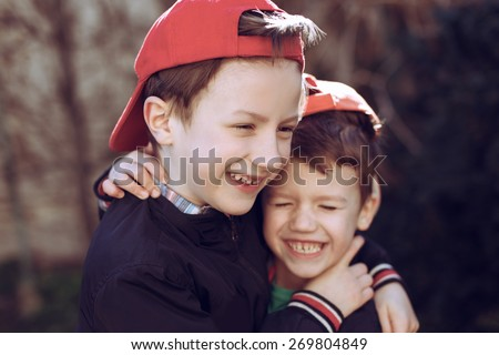 Little brothers in cap, outdoor portrait - stock photo