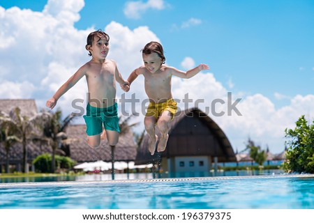 Little brothers jumping into swimming pool while they are holding their hands - stock photo