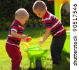 Little brothers playing in the garden. - stock photo