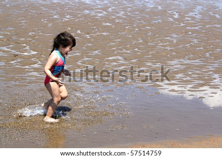 Little brunette girl in pink and blue bathing suit splashing in the water having fun  at New River beach, New Brunswick, Canada - stock photo