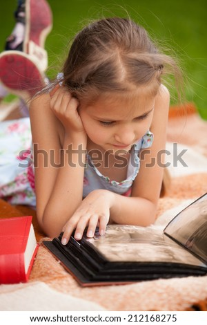Little brunette girl lying at park and looking at family photo album - stock photo