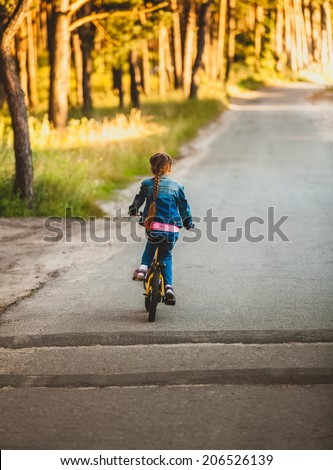 Little brunette girl riding bicycle on road at forest at sunset - stock photo