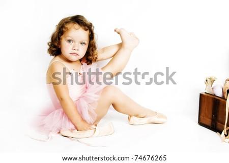 Little brunette girl trying on ballet shoes - stock photo