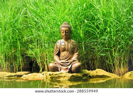 Little Buddha, sitting on the rocks near the pond with reeds - stock photo