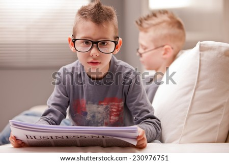 little business baby reading shocking news ready to face the shock - stock photo