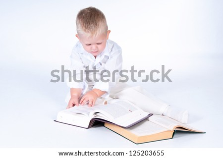 Little business man in solid white suit reads books - stock photo