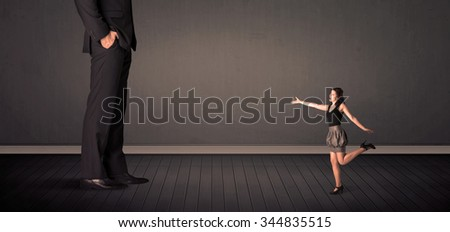 Little business woman in front of a giant boss legs concept on background - stock photo