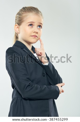 Little business woman thinking. Idea. Studio portrait of child girl in business style. Studio isolated gray background. - stock photo