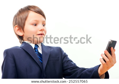 Little businessman. Confident little boy in suit looking at the screen of his phone in surprise while standing isolated over white background - stock photo
