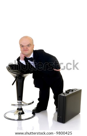 Little businessman, dwarf in a formal suit with bow tie next to bar stool and suitcase, studio shot, white background - stock photo