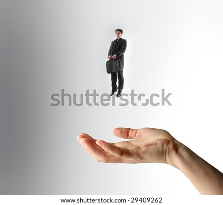 little businessman flying and a big hand under him - stock photo