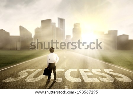 Little businessman looking for success and standing on the highway of a skyscraper with cityscape - stock photo