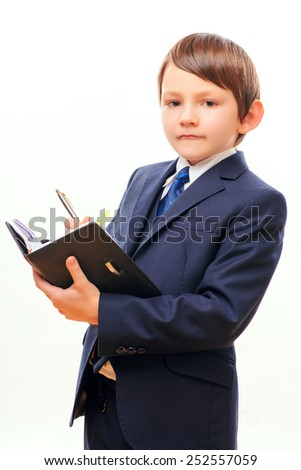 Little businessman. Side view image of confident little boy in suit holding a thick notebook and making notes while standing over the white background - stock photo