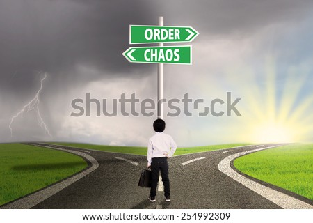 Little businessman standing on the road looking at signpost of order and chaos - stock photo