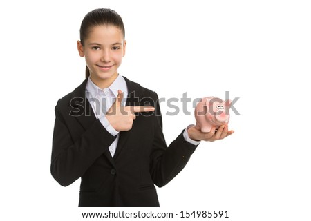 Little businesswoman with piggy bank. Cheerful little girl in formalwear holding piggy bank and pointing it while standing isolated on white - stock photo