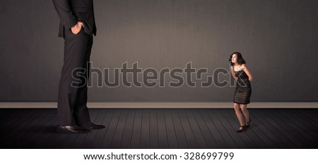 Little bussineswoman in front of a giant boss legs concept on background - stock photo