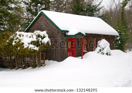 Little cabin coated in snow offers shelter from the cold - stock photo