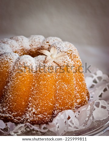 Little cake (gugelhupf) decorated with powdered sugar and little gumpaste flower. Selective focus on sugar flower - stock photo