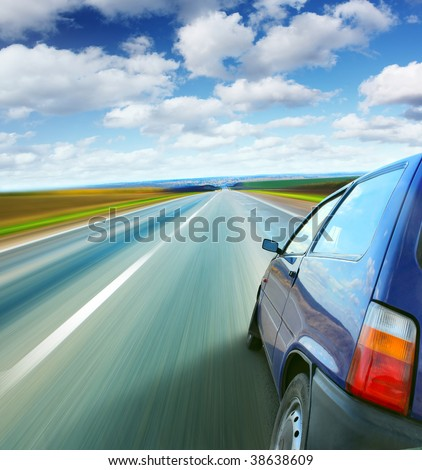Little car on a blurry road under blue sky - stock photo