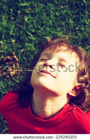 Little carefree girl playing on the grass in the park breathing fresh air. childhood concept. filtered image  - stock photo