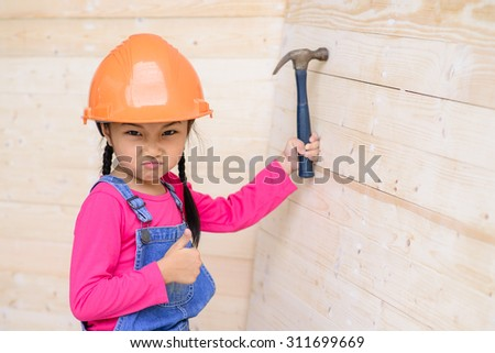 Little carpenter girl work hammer on wood and make a thumb up