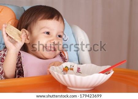 Little Caucasian baby eats at the table
