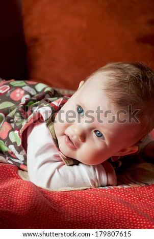 Little caucasian baby girl lying on her stomach.