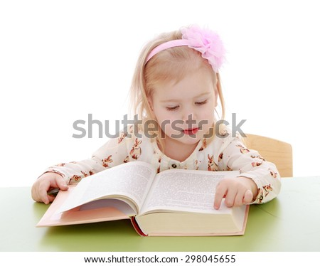 Little Caucasian blond girl sitting at a Desk and read by syllables thick academic book , the girl is preparing to go to school-Isolated on white - stock photo