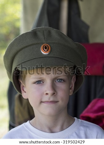 Little Caucasian boy in cap officer of the White Army during the Civil War 1917 - 1921 in the Russian Empire - stock photo