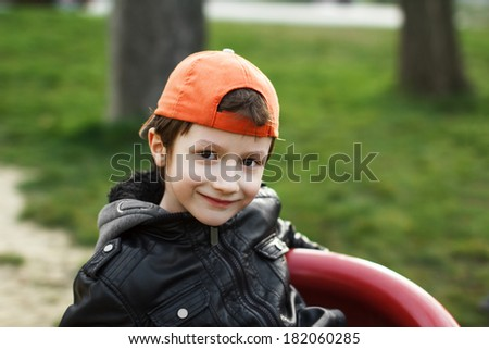 Little caucasian boy in cap smile outdoor portrait