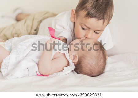 Little Caucasian Boy Kissing His Newborn Sister. Indoors Shot. Horizontal Image - stock photo