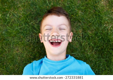 Little caucasian boy laughing in grass, outdoor portrait - stock photo