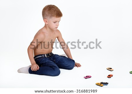 little caucasian boy playing with colorful toy cars - stock photo