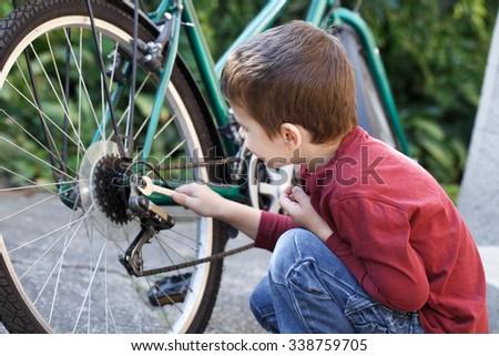Little caucasian boy repair bicycle outdoor - stock photo