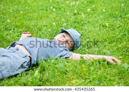 Little caucasian boy resting on grass - stock photo