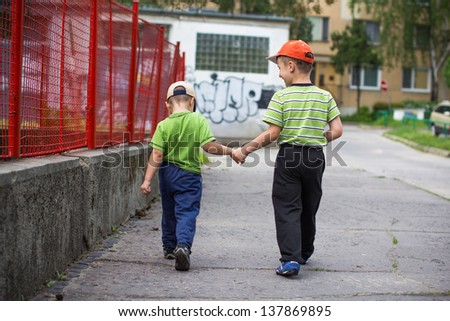 Little caucasian boys walking on sidewalk - stock photo