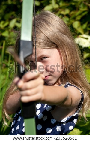 little caucasian girl aiming arrow from big bow on green garden outdoor background - stock photo