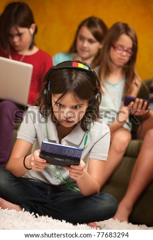 Little Caucasian girl focused on her portable gaming console - stock photo
