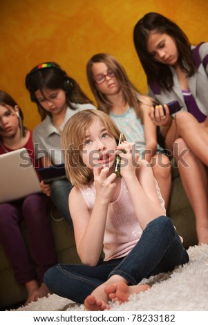 Little Caucasian girl on a serious phone call with friends behind her - stock photo