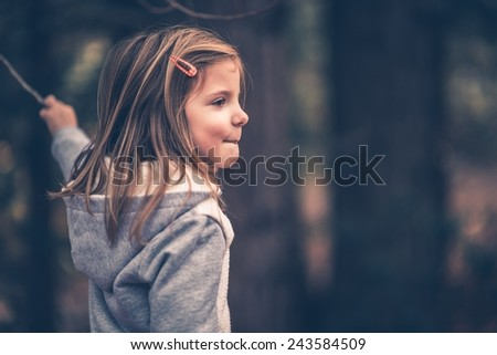 Little Caucasian Girl Playing with Small Stick. Vintage Purple Color Grading. - stock photo