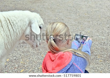 little Caucasian girl taking a selfie with goat
