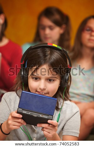 Little Caucasian girl with earphones plays a handheld video game - stock photo