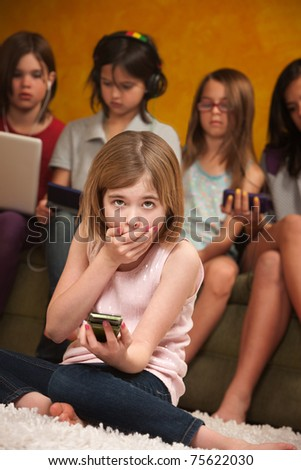 Little Caucasian girl with handheld device covers her mouth - stock photo