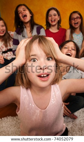 Little Caucasian girl with hands on head while friends laugh - stock photo