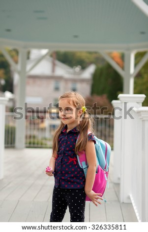 little caucasian girl with pony tails and backpack going to school - stock photo