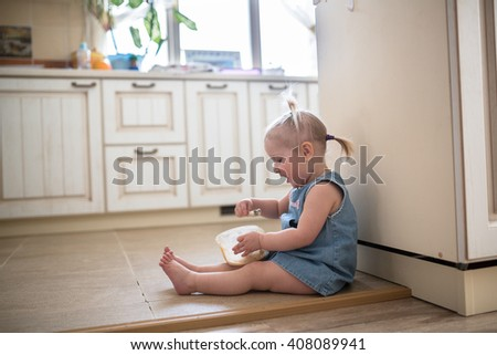 Little Caucasian Toddler funny girl with pigtails eating ice cream from a jar sitting on the floor in the kitchen, casual lifestyle photo series in real life interior - stock photo