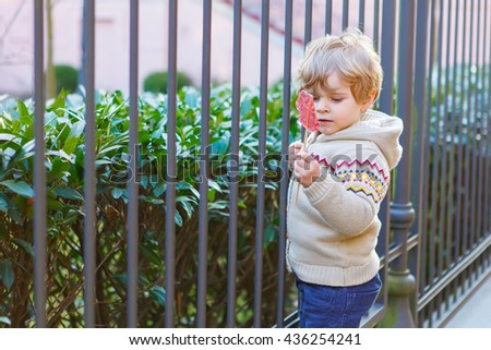 Little caucasian toddler kid boy of two years having fun in spring city, outdoors. Child eating candy - stock photo